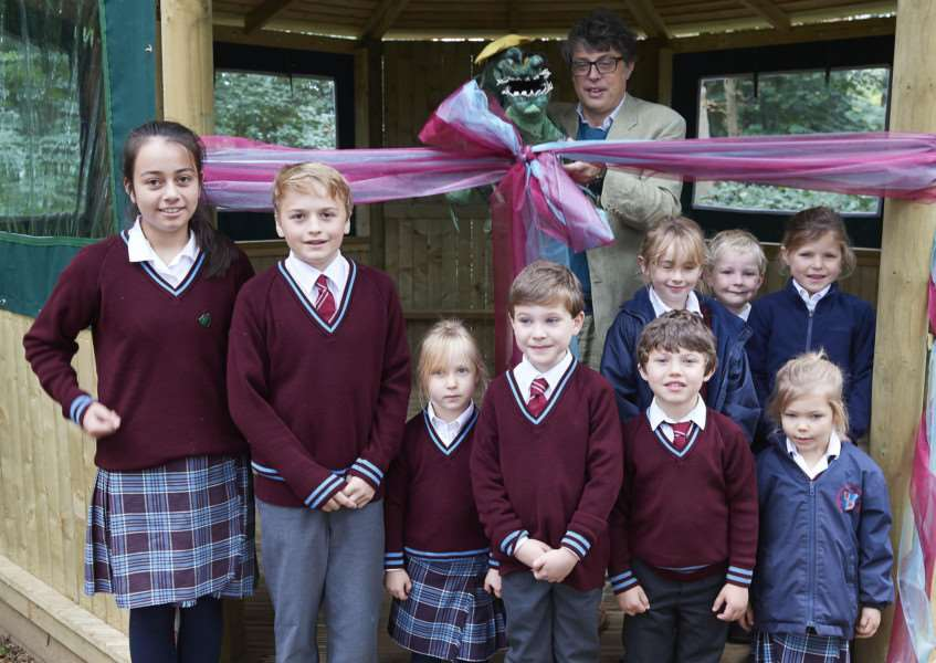 Tom Blofeld cuts the ribbon on the new outdoor cabin classroom for pupils at Riddlesworth Hall School.