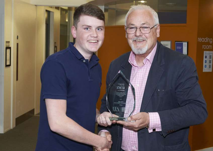 Norwich Business School student Joshua Knight receives his award from Matrin Goymour, chief executive of the Zoological Society of East Anglia.