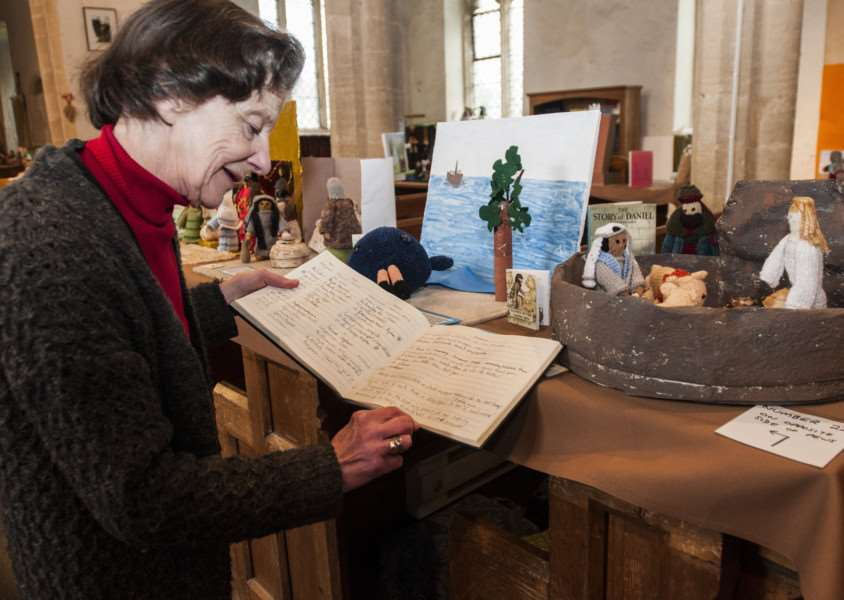 Jenny Vere and others have created over 50 bible scenes out of knitted figures and props to be displayed in St Nicholas Church, North Lopham. Jenny Vere with the vistots book