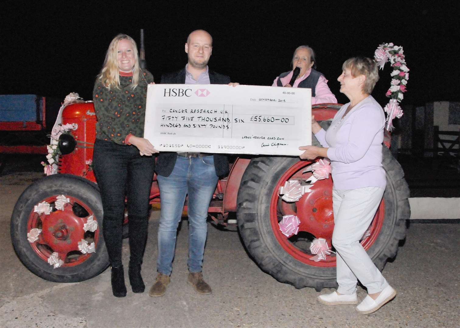 Nicholas Whymark, Alex Horne from Cancer Research UK with tractor run organiser, Annie Chapman, and Carol Wiles presenting the cheque.