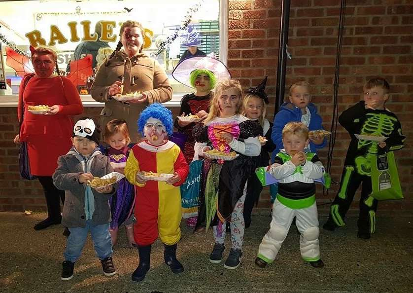 Children in costumes enjoy free sausage and chips from Baileys Fish and Chip shop. Submitted picture.