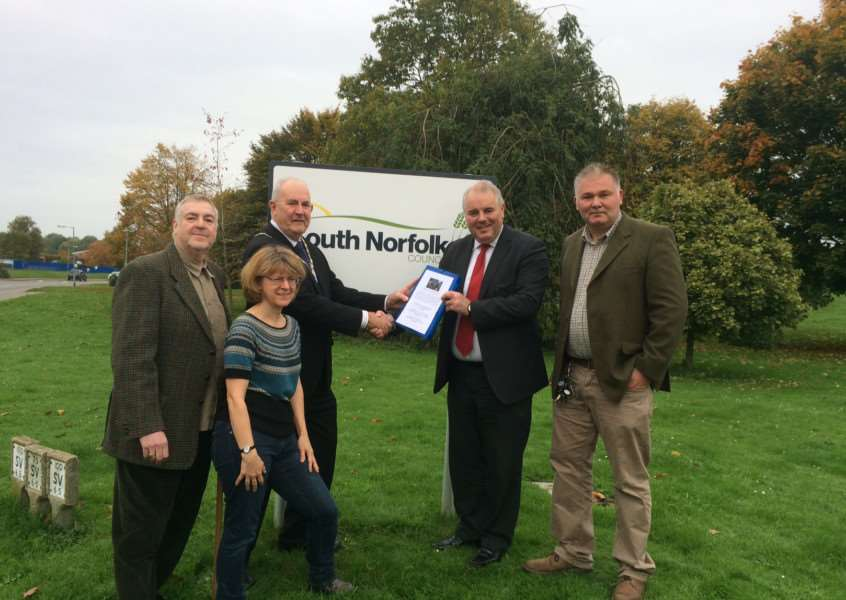 District Councillor Clayton Hudson (right) and South Norfolk MP Richard Bacon hand over the petition to the chairman of South Norfolk Council, David Bills. Submitted photo. ANL-151027-172657001