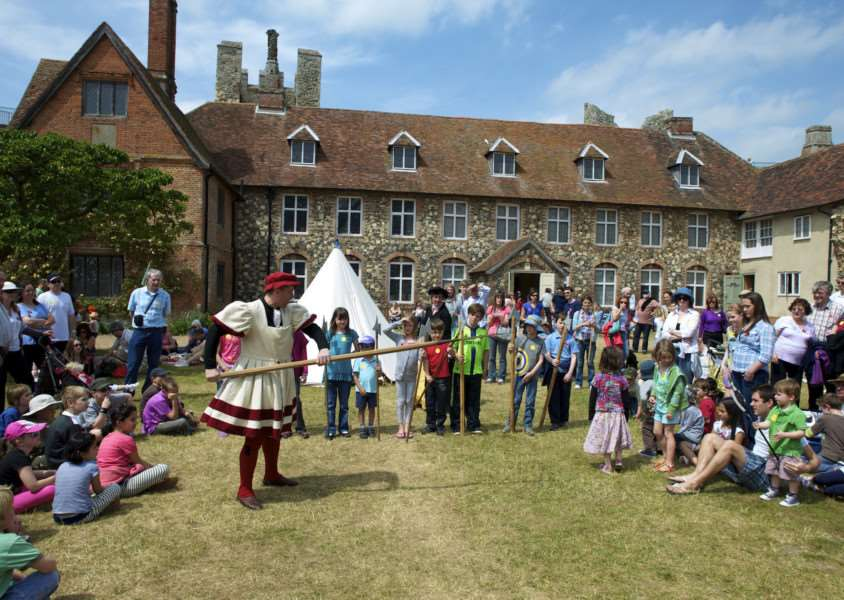 Framlingham, Suffolk. Tudor Day in the grounds of Framlingham Castle - Neil McGurck as Nelkin of Griffin Historical teaches children about the Queens Body Guard in Tudor England