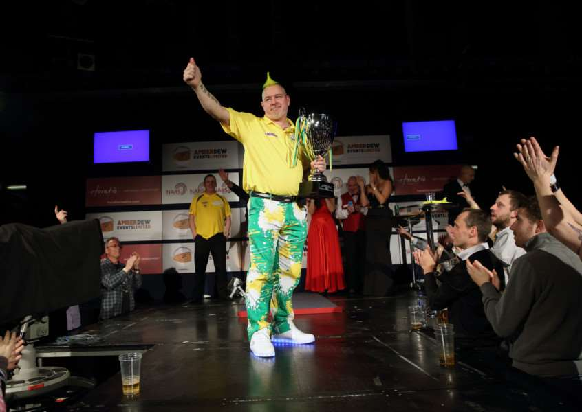 POPULAR WINNER: Mendham's Peter Wright is congratulated after winning the inaugural Norwich Match Play Darts Championship at the weekend. Inset left: Peter shows off his trophy. Photo: Julia Holland