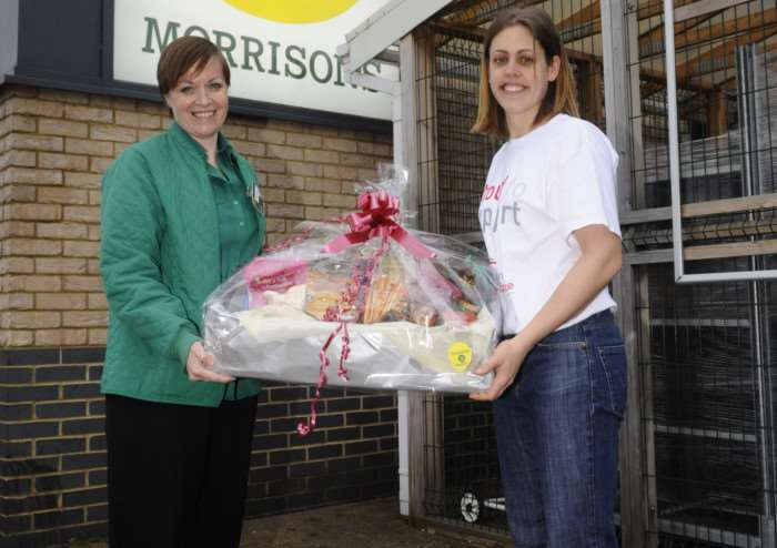 Laura Button receives a hamper from Ruth Harris-Orford, as a raffle donation, as her husband Shaun is running the London Marathan for charity.
