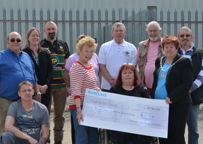 Outgoing Attleborough town mayor Karen Pettitt (right) presents cheque for �1,1770 to ShootAbility, along with members of the Attleborough Lions Club.