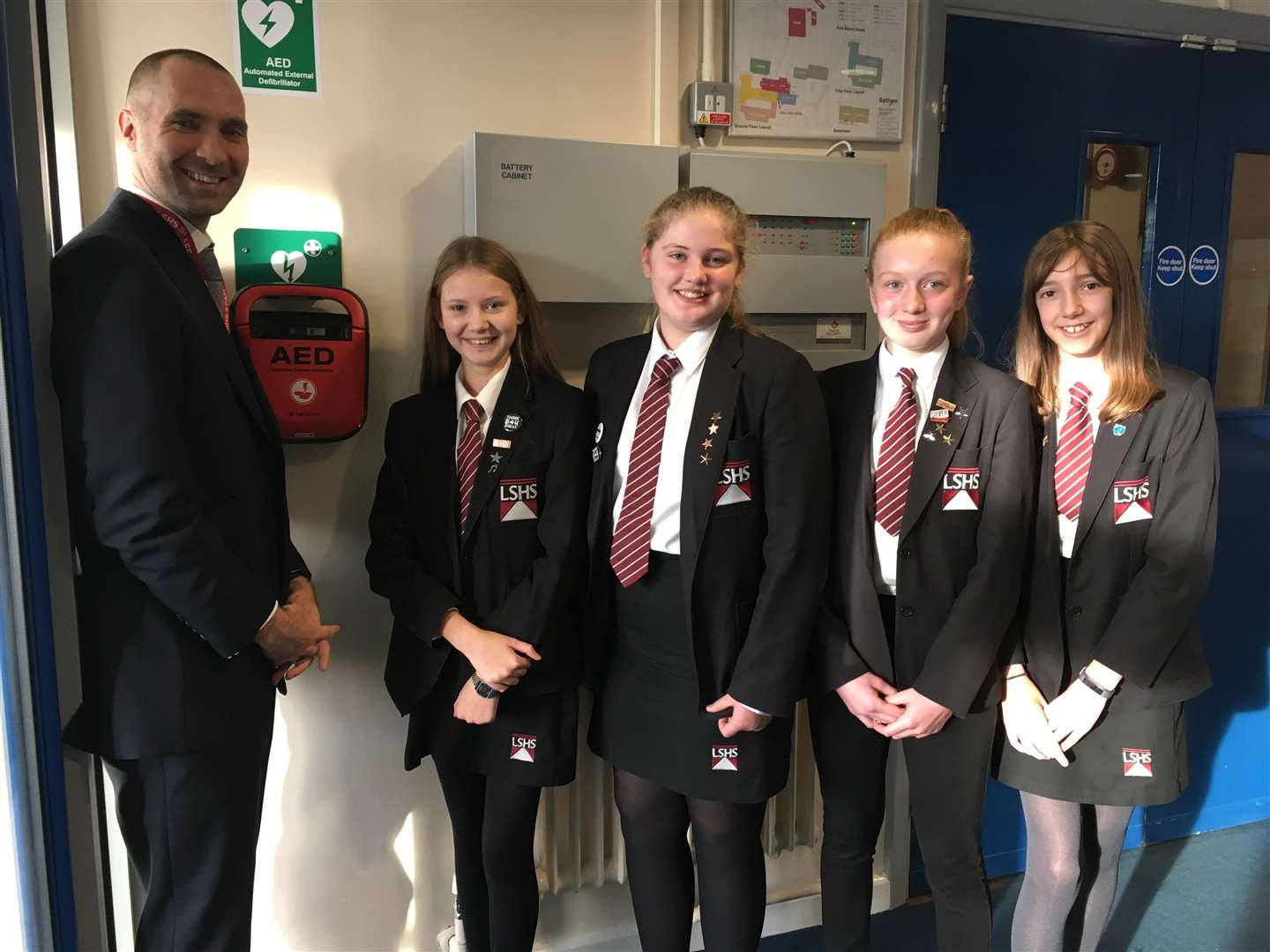 Bethany (far right) with her friends and headteacher Dr Roger Harris, celebrating the installation of the new defibrillator.